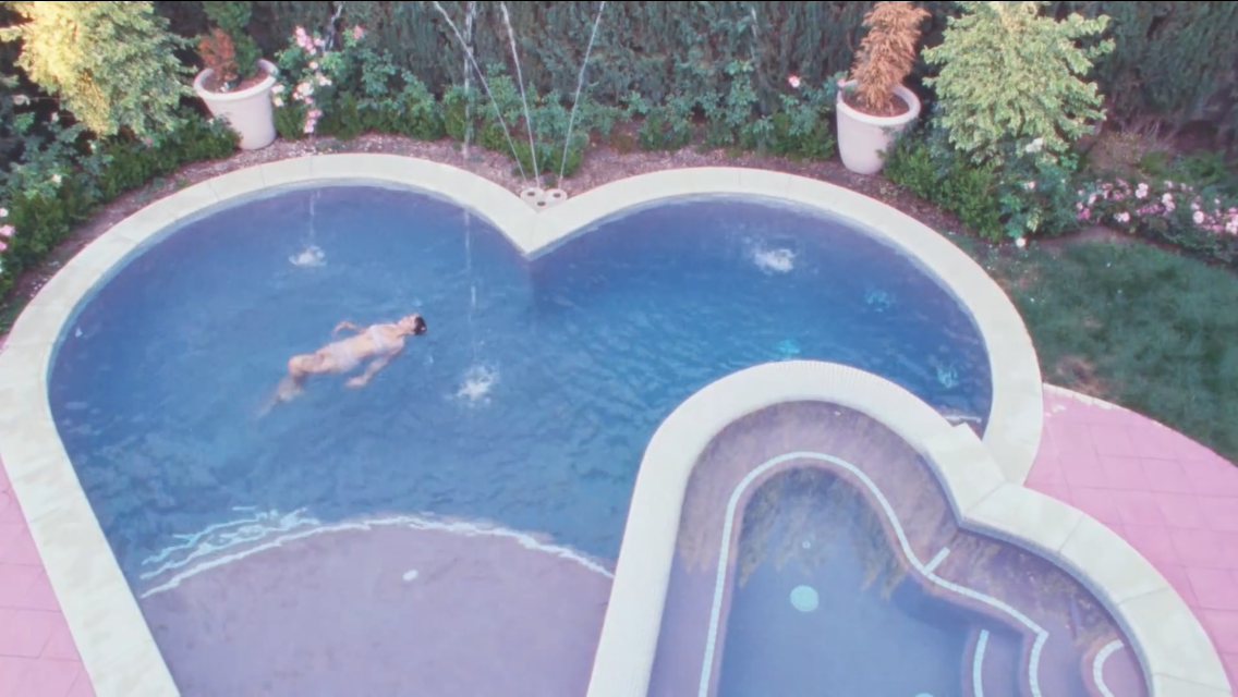 A young woman enjoys swimming in valentine heart shaped swimming pool and spa