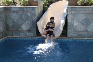 Two young boys enjoy sliding into the grandparents backyard pool