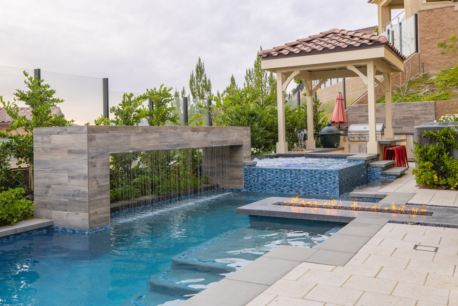 Contemporary pool design with waterfall feature and perimeter overflow spa