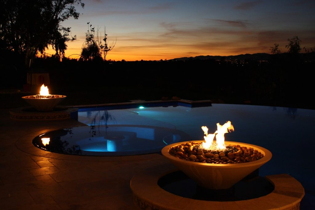 Fire features by a vanishing edge swimming pool in the sunset