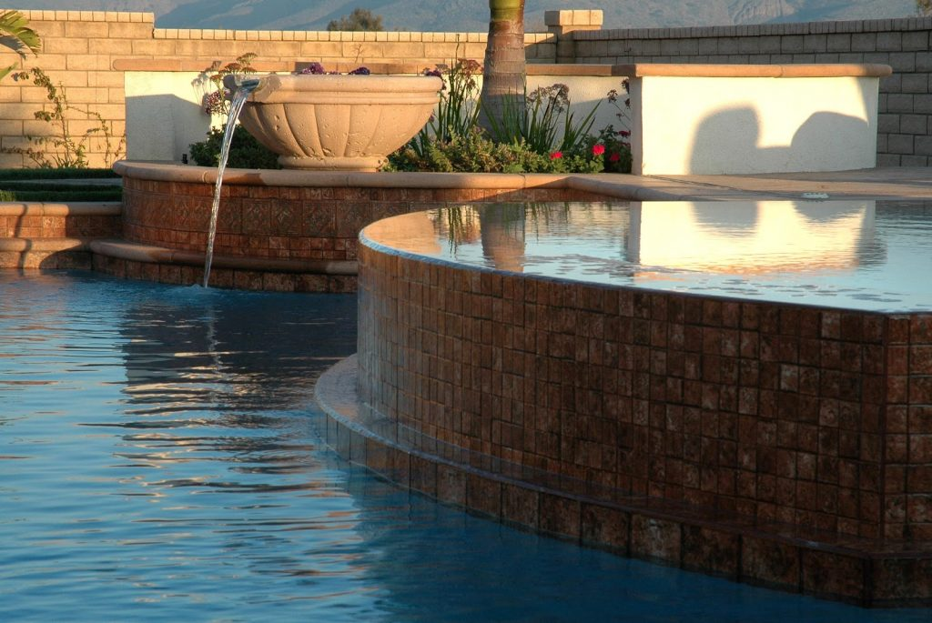 A perimeter overflow spa by a swimming pool and a water fountain feature