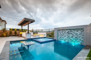 A small backyard with a glowing contemporary pool, built-in chess table, outdoor kitchen and fire pit