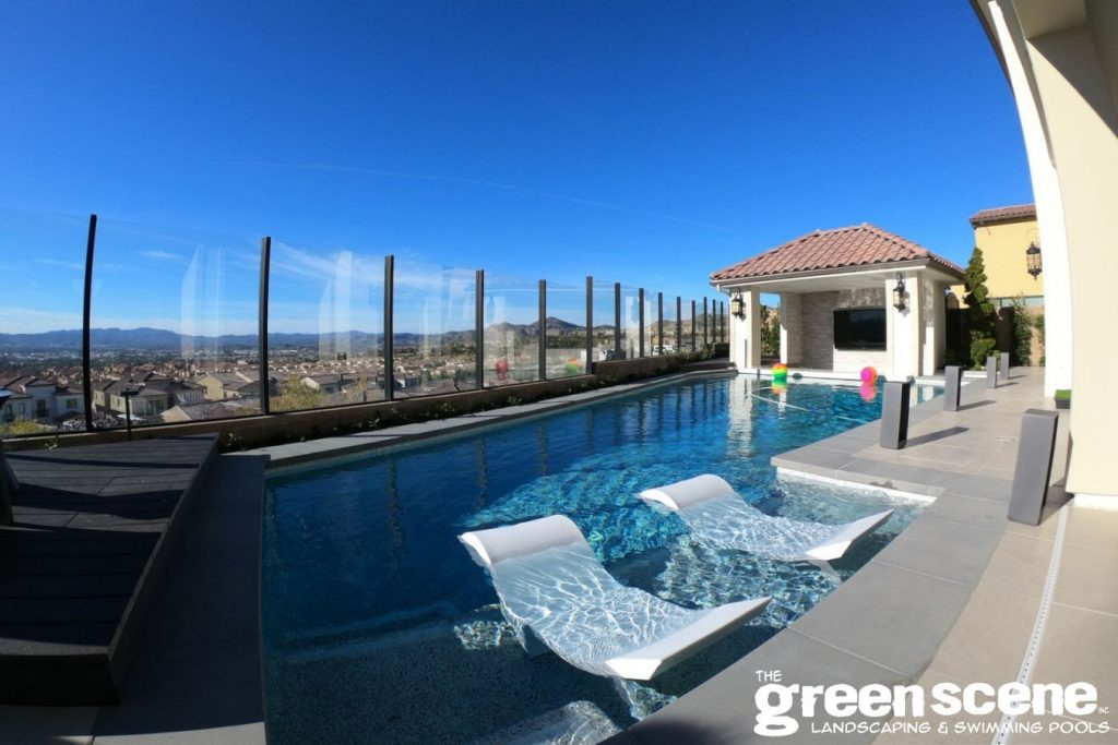 Contemporary pool design with baja shelves and a view of the city