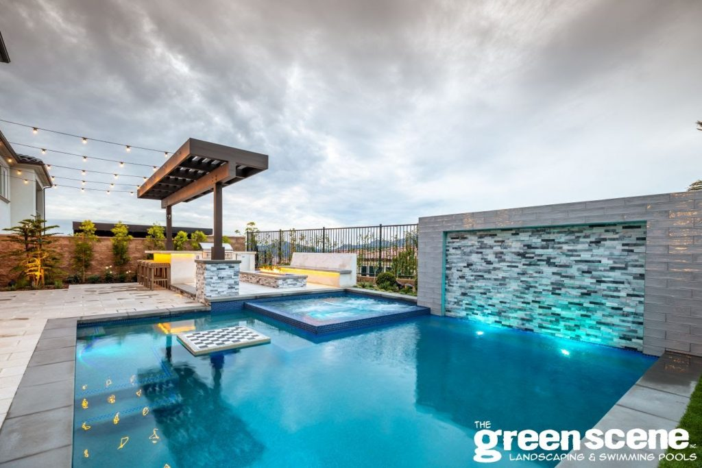 Small contemporary swimming pool with an in-pool chess table and fire pit and outdoor kitchen