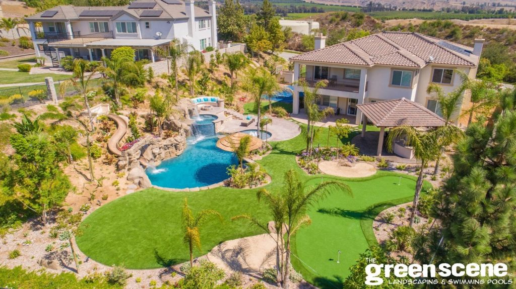 A bad-ass backyard has stunning features like a pool, slide, faux golf turf, spa, and outdoor kitchen
