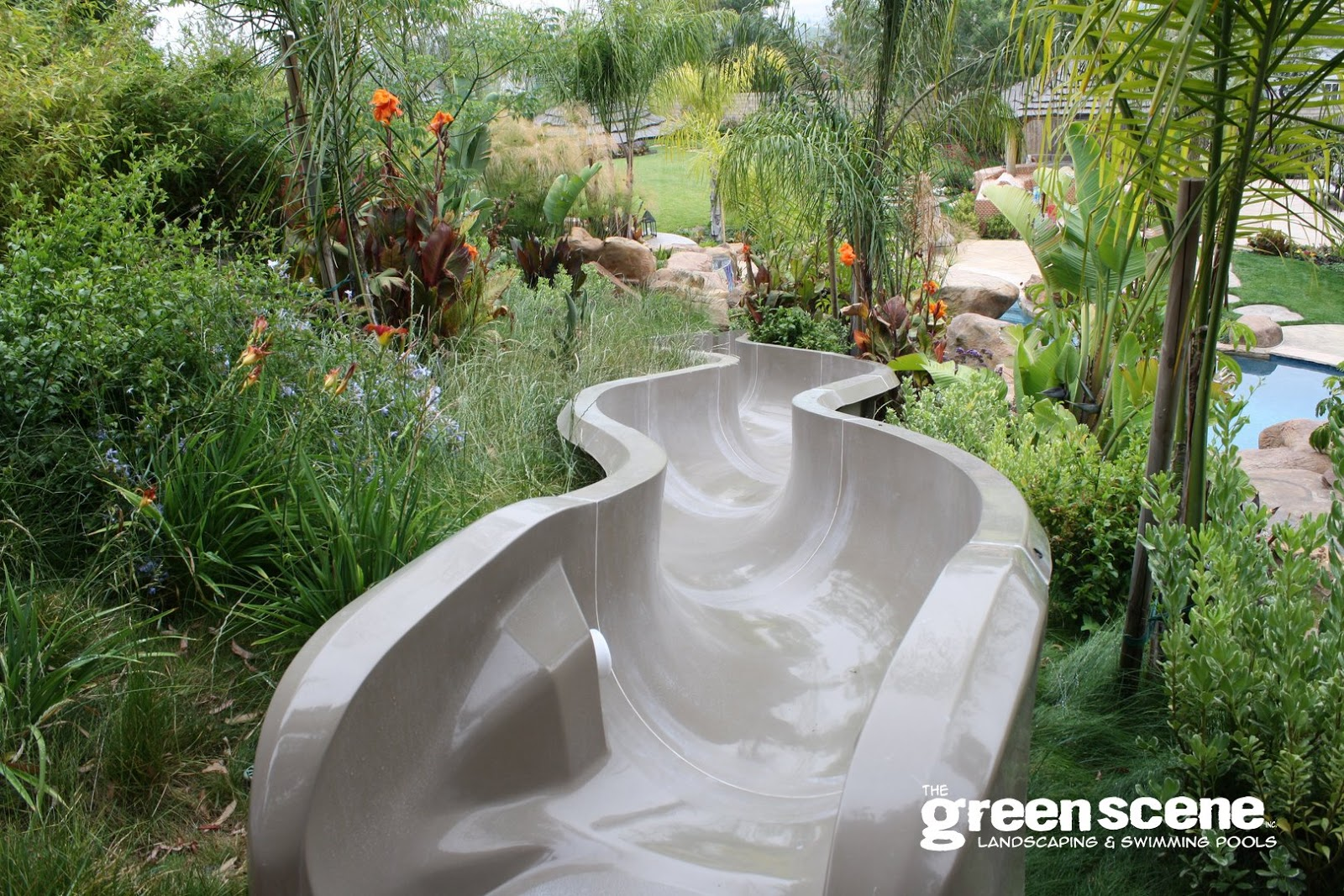 A large backyard playground slide flows into a swimming pool in exotic style landscaping