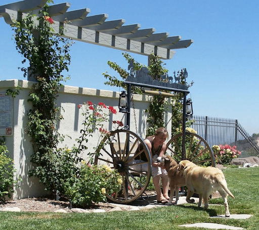 A woman sits with her two dogs in a yard landscaped for pets