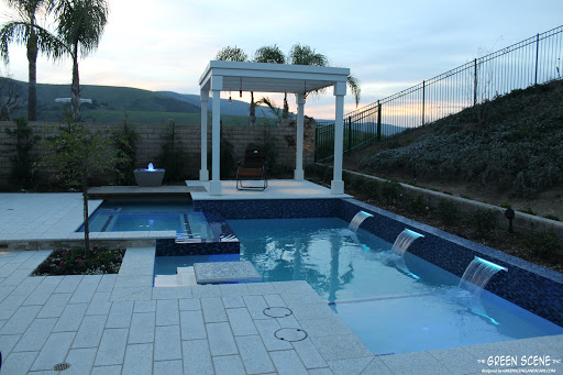a built-in pool table in a contemporary pool design at sunset