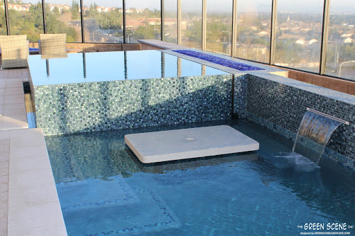 an infinity-edge spa in a contemporary pool with a built-in table