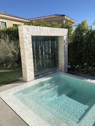 a sleek waterfall feature in a contemporary pool design