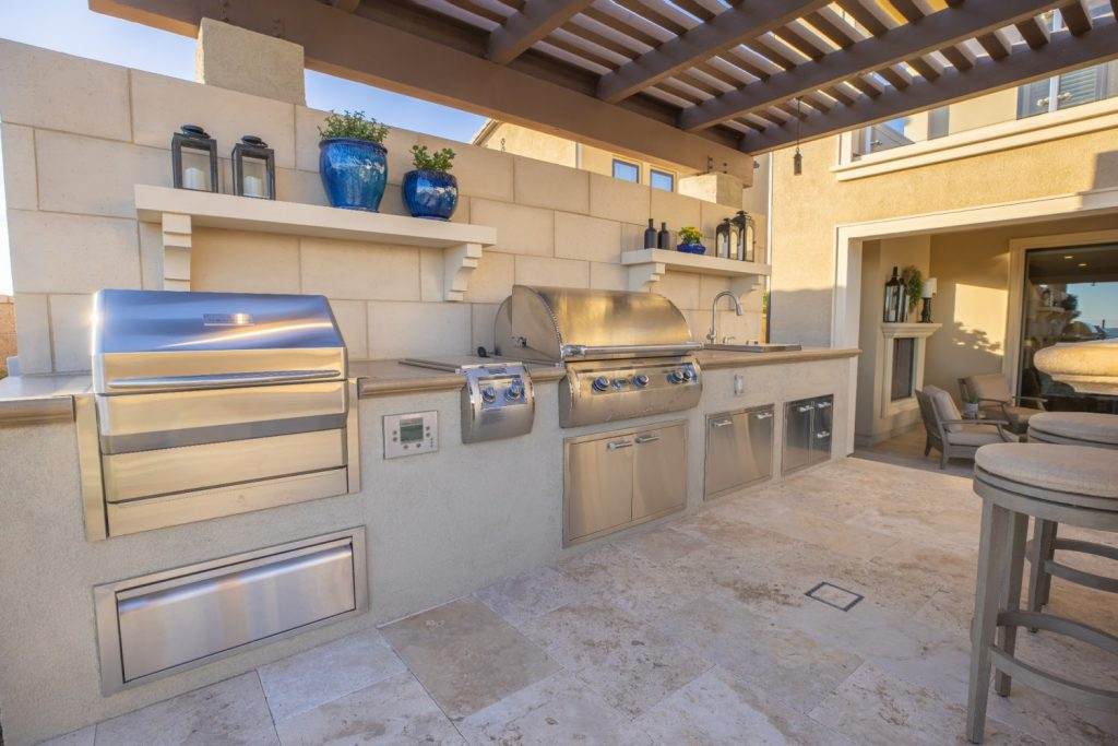 Outdoor kitchen with grill, cooler, stovetop, sink, and outdoor seating