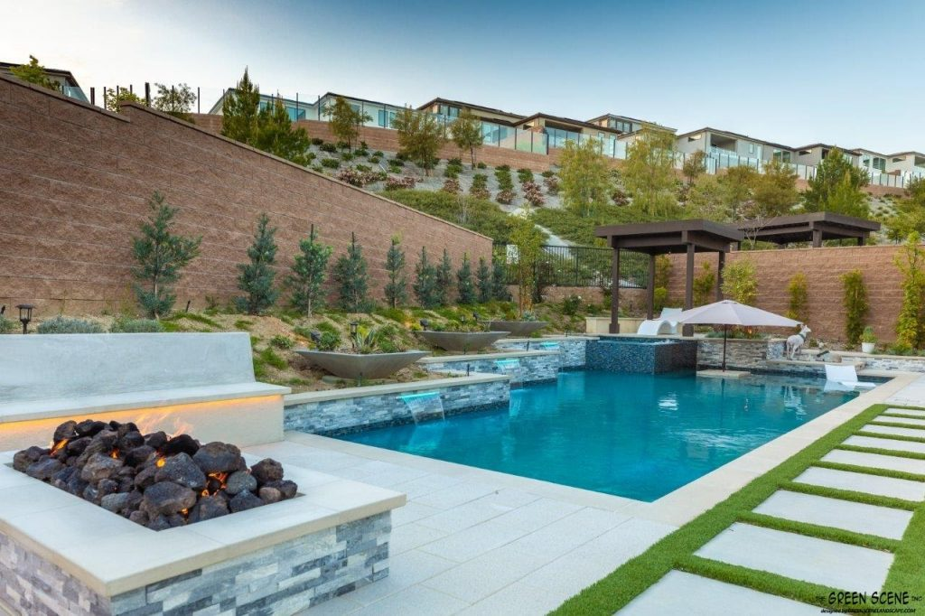 A villa complete with contemporary pool, hardscaping, and privacy landscaping